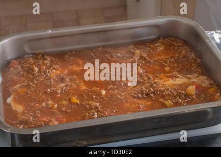 In Vorbereitung ist ein Edelstahl Tablett mit den Zutaten ist eine hausgemachte Lasagne über bereit, in den Ofen zum Backen. - Stockfoto