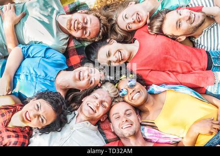 Gruppe von diversen Freunden Spaß im Freien - Glückliche junge Menschen, die auf Gras nach Picknick und zusammen lachen - Stockfoto