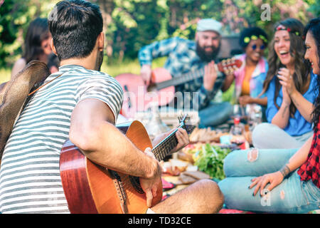 Junge Leute, Picknick und Gitarre spielen im Park - Gruppe der glücklichen Freunde Spaß haben während des Wochenendes im Freien - Stockfoto