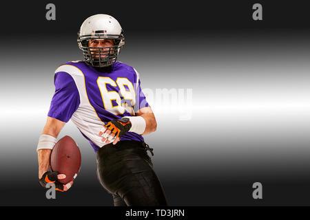 Konzept American Football, American Football Spieler mit Ball in Hand. Schwarz Weiß Hintergrund, kopieren. American football Sportler Spieler in - Stockfoto