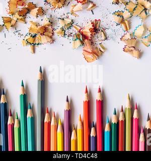 Reihe der farbigen geschärft Buntstifte und farbige Späne auf Papier Hintergrund - Stockfoto