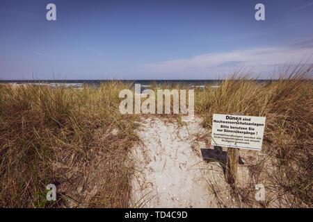 Ein Schild mit einem Warnschild steht an der Düne von der Ostsee Se - Stockfoto