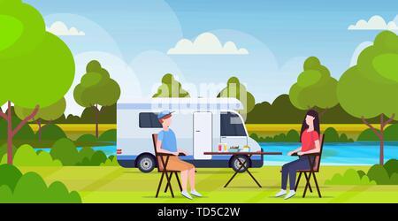 Paar am Tisch in der Nähe von Camping familie Lkw-anhänger caravan Auto Mann Frau spendingtime zusammen Sommerferien Konzept wunderschöne Natur Landschaft sitzen - Stockfoto