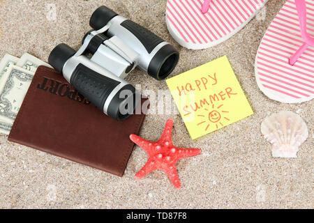 Zusammensetzung mit Flip-flops, Fernglas, Notizblock und Geld, auf Sand Hintergrund - Stockfoto