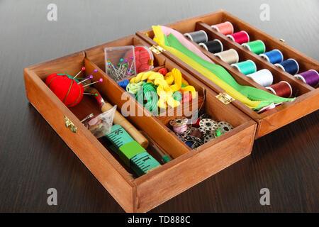 Nähset im Holzkasten auf hölzernen Tisch - Stockfoto