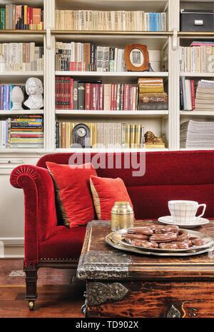 Couchtisch aus Schatztruhe mit Hand geschmiedetem Eisen Hardware vor rotes Sofa und Bücherregal im Wohnzimmer britische und irische NUR RECHTE - Stockfoto