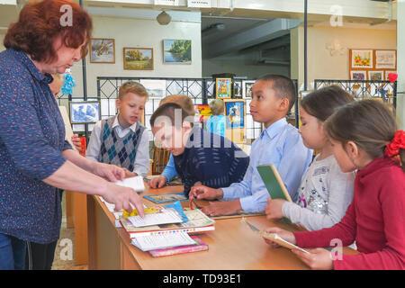 An der Volksschule. Frau Lehrerin mit Grundschülern. Schule Kinder sind neben den Schreibtisch der Lehrer - Stockfoto