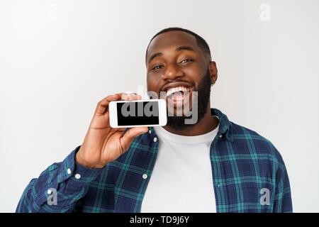 Schönen afrikanischen Kerl auf grauem Hintergrund isoliert, präsentiert smart phone und zeigte mit dem Finger auf leeren schwarzen Bildschirm. - Stockfoto