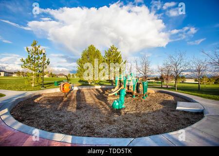 Spielplatz in der Mitte des kreisförmigen Bahn und weites Feld mit Bäumen. In der Ferne die Häuser und den Berg kann gegen den bewölkt blauer Himmel auf dieser gesehen werden. - Stockfoto
