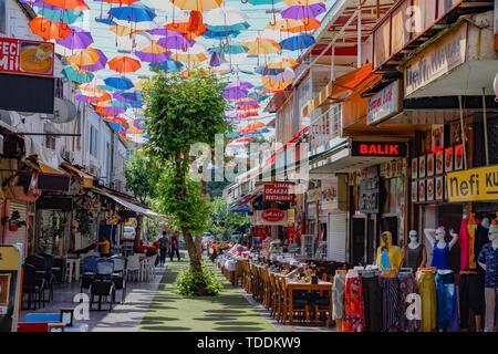 Antalya, Türkei - 19. Mai 2019: Straße in Kaleici mit Sonnenschirmen zwischen Gebäuden ausgesetzt. - Stockfoto