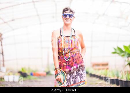 Fröhliche glückliche junge blonde Frau lächeln und für hippy Kleidung Porträt Pose - Glück und farbenfrohen Lebensstil für alternative Menschen outdoor-trendy - Stockfoto
