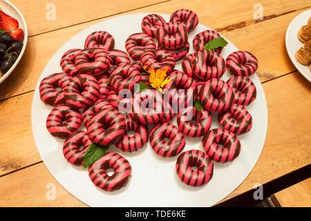 Leuchtend rosa und braun Donuts auf einem weißen runden Glas Fach mit gelben Margarita Blumen und Blätter Minze dekoriert - Stockfoto