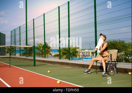 Schlankes junges Mädchen Athlet tennis player ist auf dem offenen Tennisplatz im Sommer. Wischt sich den Schweiß mit einem Handtuch nach dem Spiel und setzt sich auf einen Stuhl. - Stockfoto