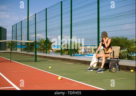Schlankes junges Mädchen Athlet tennis player ist auf dem offenen Tennisplatz im Sommer. Müde und auf dem Stuhl nach dem Spiel - Stockfoto