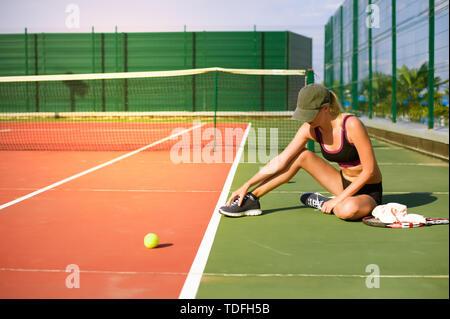 Schlankes junges Mädchen Athlet tennis player ist auf dem offenen Tennisplatz im Sommer. Sitzt und berührt den wunden Punkt stretching auf dem Fuß - Stockfoto