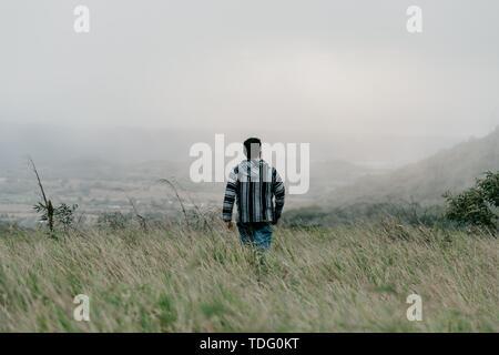 Ein Kerl, der im Feld durch Gras an einem trüben nebligen Tag trägt ein Flanell - Stockfoto