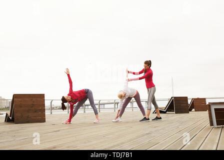 Weitwinkel Portrait von älteren Frauen Yoga im Freien während der Morgen Klasse am Pier, kopieren Raum - Stockfoto