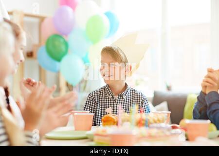 Portrait von lächelnden Jungen tragen Krone sitzen am Tisch beim Feiern Geburtstag mit Freunden, kopieren Raum Stockfoto