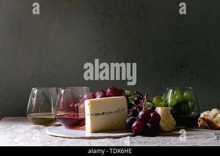 Vielzahl von Wein. Rotwein, Rosé und Weißwein in Old Fashion Brille mit Weintrauben, Blauschimmelkäse auf Keramik und Brot auf grau Bettwäsche Tisch cl - Stockfoto