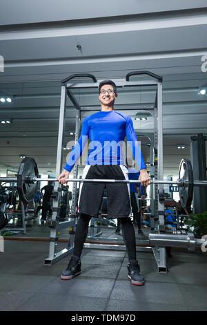 Junge asiatischer Mann sie im modernen Fitnessraum arbeiten - Stockfoto