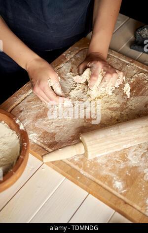 Frau bereitet den Teig auf der Arbeitsfläche mit Mehl und Nudelholz auf weissem Holztisch - Stockfoto