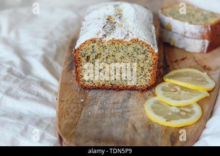 Kuchen mit Mohn und Zitronenschale, bestreut mit Puderzucker. Cupcake mit Zitrone auf einem Holzbrett - Stockfoto