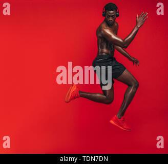 Afrikanische amerikanische Mann mit muskulösen Körper Ausübung auf roten Hintergrund. Geschossen von einem jungen Mann das Training im Studio. - Stockfoto