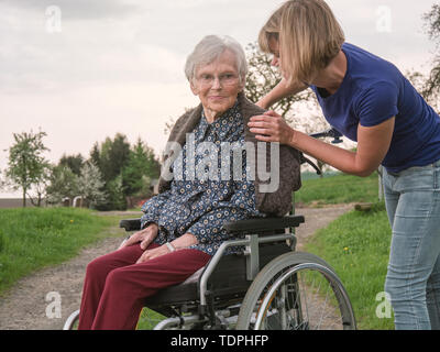 Betreuer hilft besorgt, älteren Dame im Rollstuhl - Stockfoto
