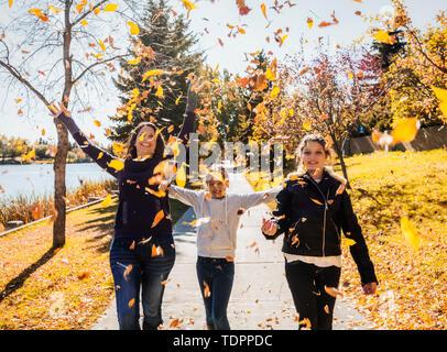 Eine Mutter und ihre zwei Töchter laufen und werfen Blätter in der Luft in einer Stadt Park an einem warmen Herbsttag; Edmonton, Alberta, Kanada - Stockfoto