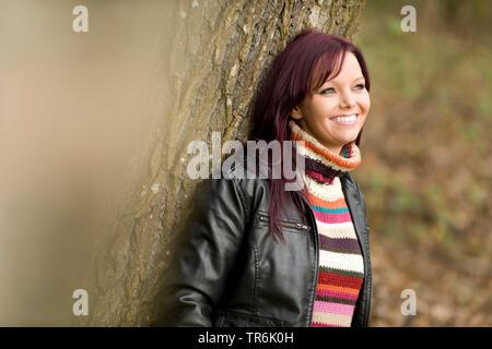 Frau lehnt sich an einem Baum - Stockfoto