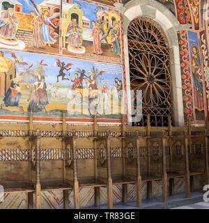 Eine Kirche, die Wände in das Rila-kloster, Bulgarien. Religiöse Fresken an der Bibel Abhandlungen, Bilder an der Wand und handgefertigte Stühle aus Holz in einer Reihe - Stockfoto
