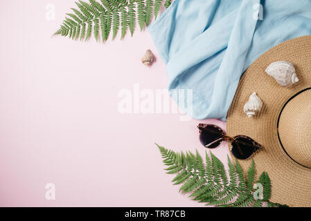 Weibliche Sommermode Komposition mit Bluse, Hut, Sonnenbrille, Farn, seashell auf rosa Hintergrund. Flach, Ansicht von oben minimalistischen Kleidung Collage. Tr - Stockfoto