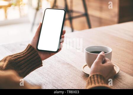 Mockup Bild der Frau Hand schwarz Handy mit leerer Bildschirm beim Trinken von Kaffee - Stockfoto