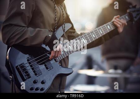Ein Straßenmusiker, in einer dunklen Jacke mit gestreiften Schnürsenkel gekleidet, spielt ein Rhythmus, der auf einem 5-String E-Gitarre, stand am Abend auf dem Platz - Stockfoto