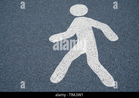 Spaziergang Zeichen, die Fußgängerzone auf einem nassen dunklen Asphaltboden - Stockfoto