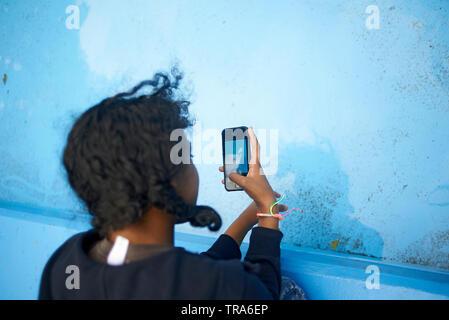 Teenage schwarze Mädchen sitzen in einem Park Bilder aufnehmen mit ihrem Mobiltelefon in einem Pool - Stockfoto