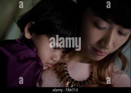 Eine junge Malay Mutter liebevoll umarmt ihren kleinen Sohn auf dem Schoß sitzt. - Stockfoto