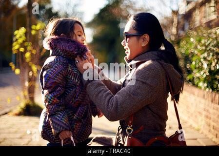 Schöne junge asiatische Mutter squating unten die Knöpfe der Wappen von ihrer kleinen Tochter im Winter Sonnenschein zu schließen. - Stockfoto