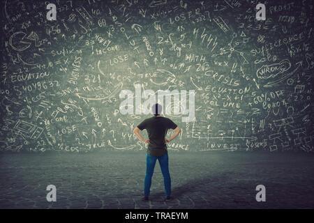 Ansicht der Rückseite des verwirrten Studenten, die Hände auf den Hüften, steht vor einer riesigen Tafel versuchen Mathematik Berechnung, Formeln und Gleichungen zu lösen. Pr - Stockfoto