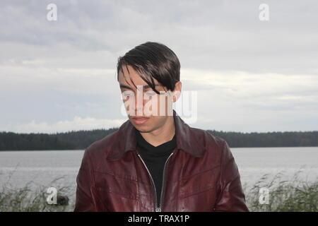 Hübscher junger Mann an einem See einen stürmischen Nachmittag in Finnland im Sommer posing - Stockfoto
