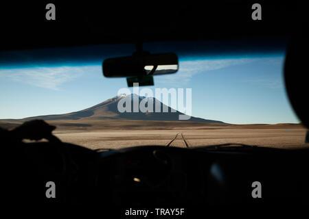 Fahren auf Feldweg in Richtung einer vulkanischen Gipfel auf dem bolivianischen Altiplano. - Stockfoto