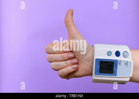 Arm und Blutdruck überwachen, am Handgelenk geknöpft. In der Mitte, in der unteren rechten Ecke. Auf einem violetten Hintergrund. Auf der Anzeigetafel Herz ra - Stockfoto