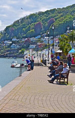Eine Gruppe junger Freunde Mageres über Hafen Kante, während die Fischerei auf Krebse. Andere Leute sitzen in der Sonne und beobachten den Fluß Verkehr. - Stockfoto