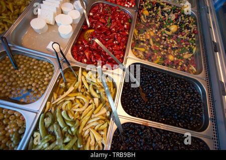 Eine große Auswahl an frischen, grünen und schwarzen Oliven und Paprika auf dem Display am Marktstand - Stockfoto