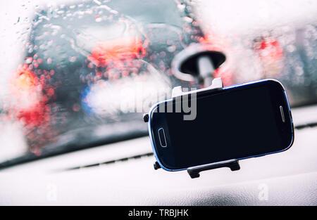 Smart Phone auf Halter, regnerischen Wetters durch Wind Schild, Handy mit schwarzen Mock up Leer auf dem Bildschirm. Werbung für Verkehr und Navigation - Stockfoto
