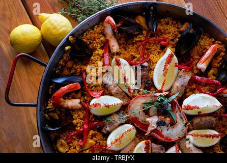 Leckere spanische Paella, Ansicht von oben. Mit stör Heilbutt-filet gekochte, geschälte Garnelen, Tintenfisch, Muscheln, Hummer mit Zitrone zu eingerichtet - Stockfoto