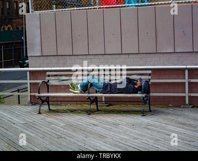 Obdachlosen schläft auf der Bank an der Strandpromenade von Coney Island, Brooklyn - Stockfoto