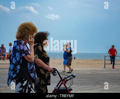 Eine ältere Frau ist Laufen mit Senioren Walker auf der Promenade in den Brighton Beach auf einer Feder am Nachmittag. - Stockfoto