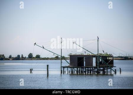 Die traditionelle Fischerei Hütte auf Stelzen mit hängenden Netzen in Comacchio Tal, Emilia Romagna, Italien. Das Fischerdorf liegt in einer Lagune, surro gelegen - Stockfoto