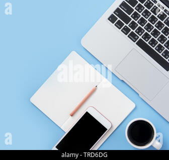 Mädchen schreibt am geöffneten weißen Buch oder auf einer minimalen sauber Hellblau Schreibtisch mit Laptop und Zubehör, Kopieren, Flach, Ansicht von oben, Mock up - Stockfoto